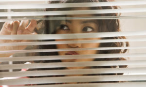 Businesswoman peering through window blinds